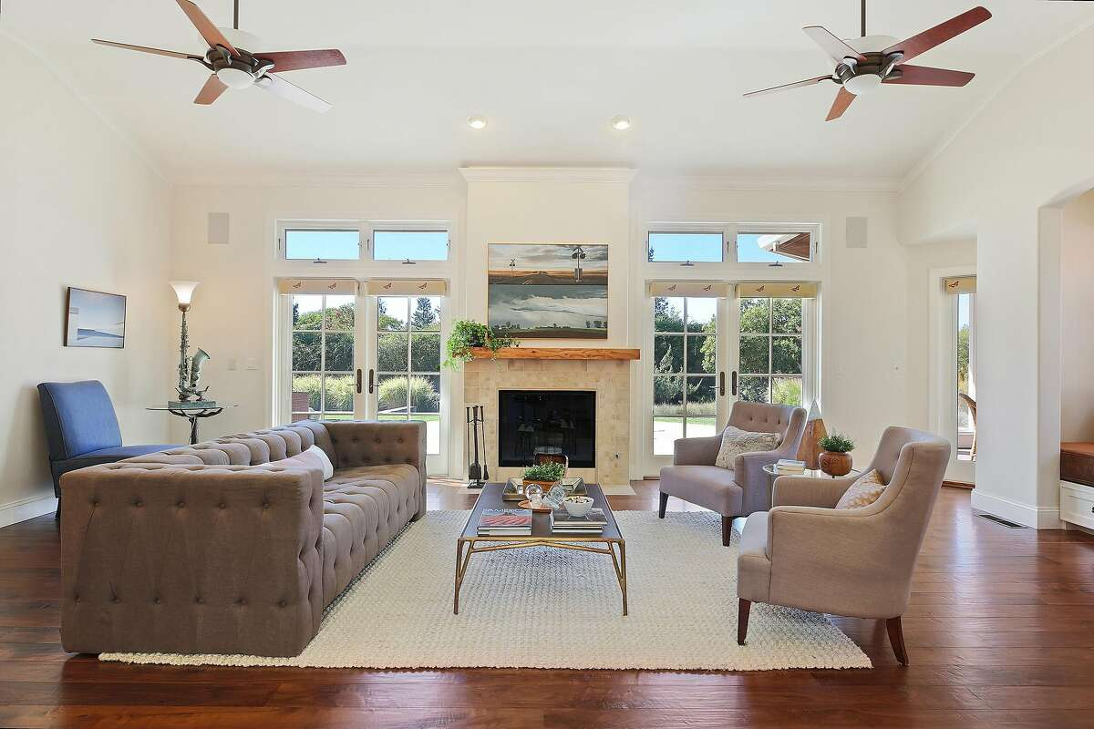The living room features a wood-burning fireplace and dual sets of French doors leading to the patio.