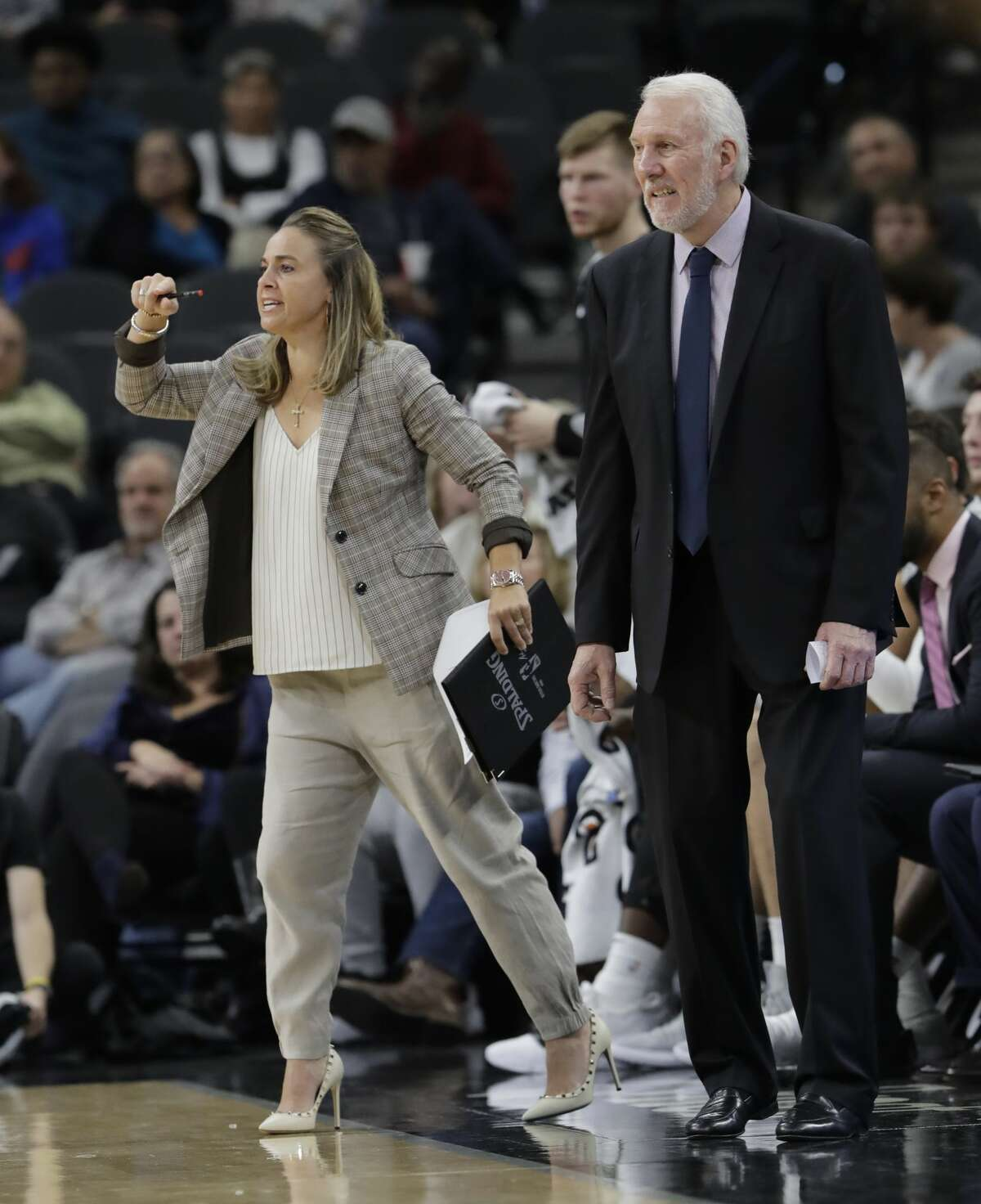 San Antonio Spurs head coach Gregg Popovich, right, and assistant coach Becky Hammon, left, during the second half of an NBA basketball game against the Minnesota Timberwolves, Wednesday, Oct. 17, 2018, in San Antonio. San Antonio won 112-108. (AP Photo/Eric Gay)