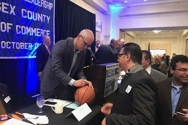 UConn men's basketball coach Dan Hurley autographs a basketball at Thursday's Middlesex County Chamber of Commerce breakfast.