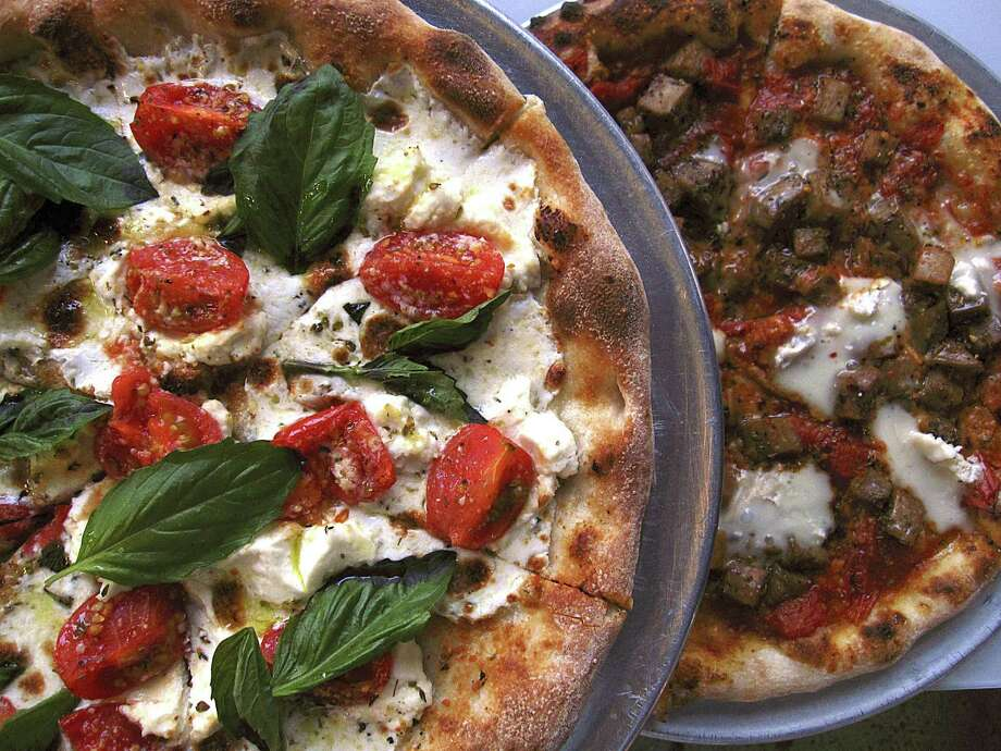 Roof Fire pizza, left, with cherry tomatoes, basil, mozzarella and ricotta and a Brie Real pizza with brie, eggplant, oregano and Campari tomato sauce from Playland. Photo: Mike Sutter /Staff