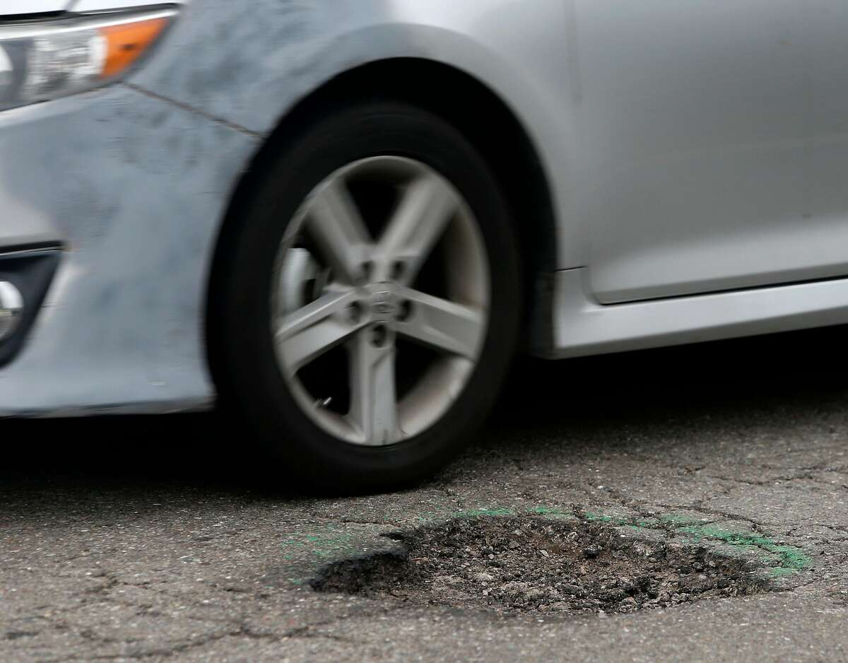 A driver narrowly avoids a pothole on Chatham Road in Oakland, Calif. on Wednesday, Feb. 15, 2017. Street maintenance crews are struggling to keep up with a large number of potholes due to the constant rain.