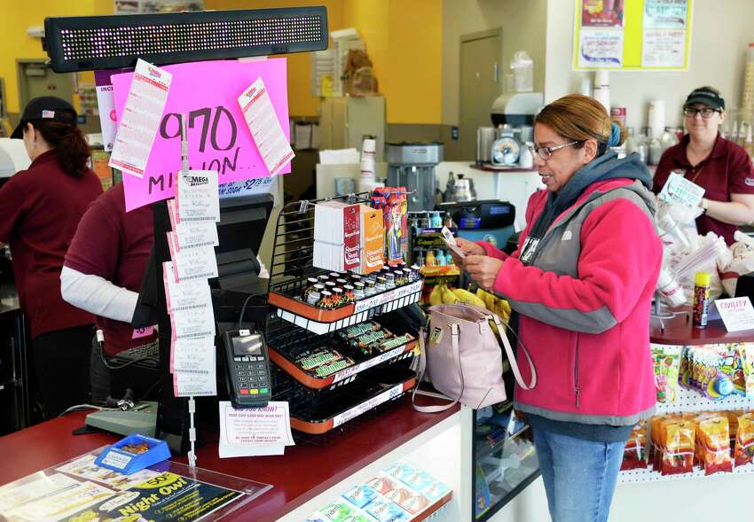 Gilda Hernandez of Clifton Park checks her Mega Millions tickets at the Vischer Ferry Stewart's Shop as the jackpot hits $970 million Thursday Oct. 18, 2018 in Clifton Park, NY. (John Carl D'Annibale/Times Union)