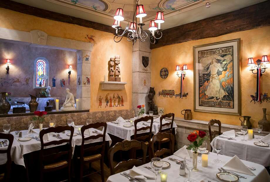 Paintings and other works of art line the walls of the dining room at Jeanne d'Arc restaurant, inside Cornell Hotel de France in San Francisco. Photo: Jessica Christian / The Chronicle