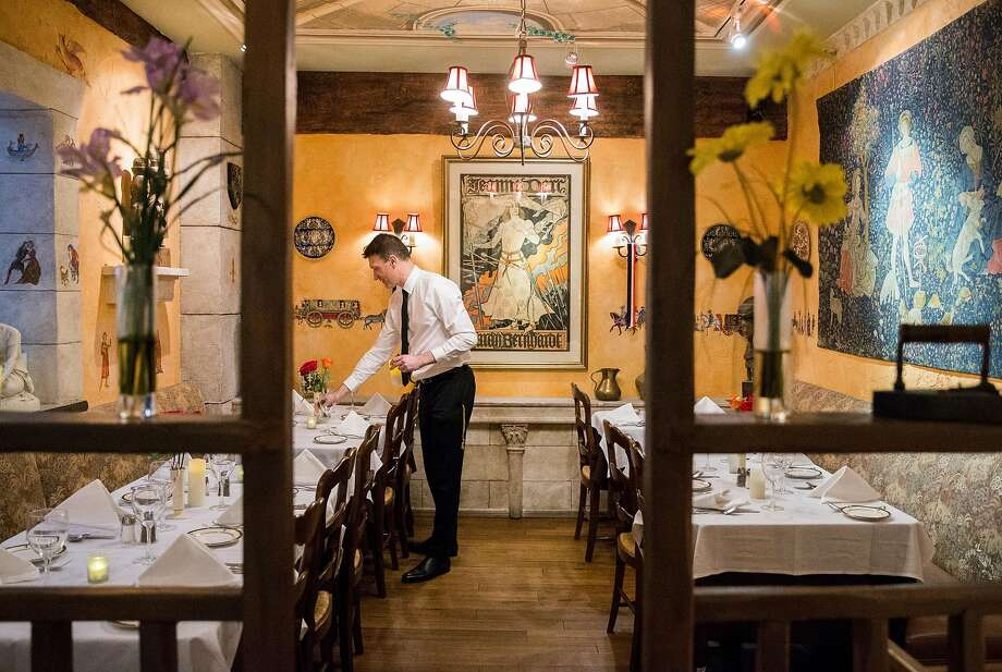 Manager Franck LeGrand prepares the dining room for guests before opening at Jeanne d'Arc. Photo: Jessica Christian / The Chronicle