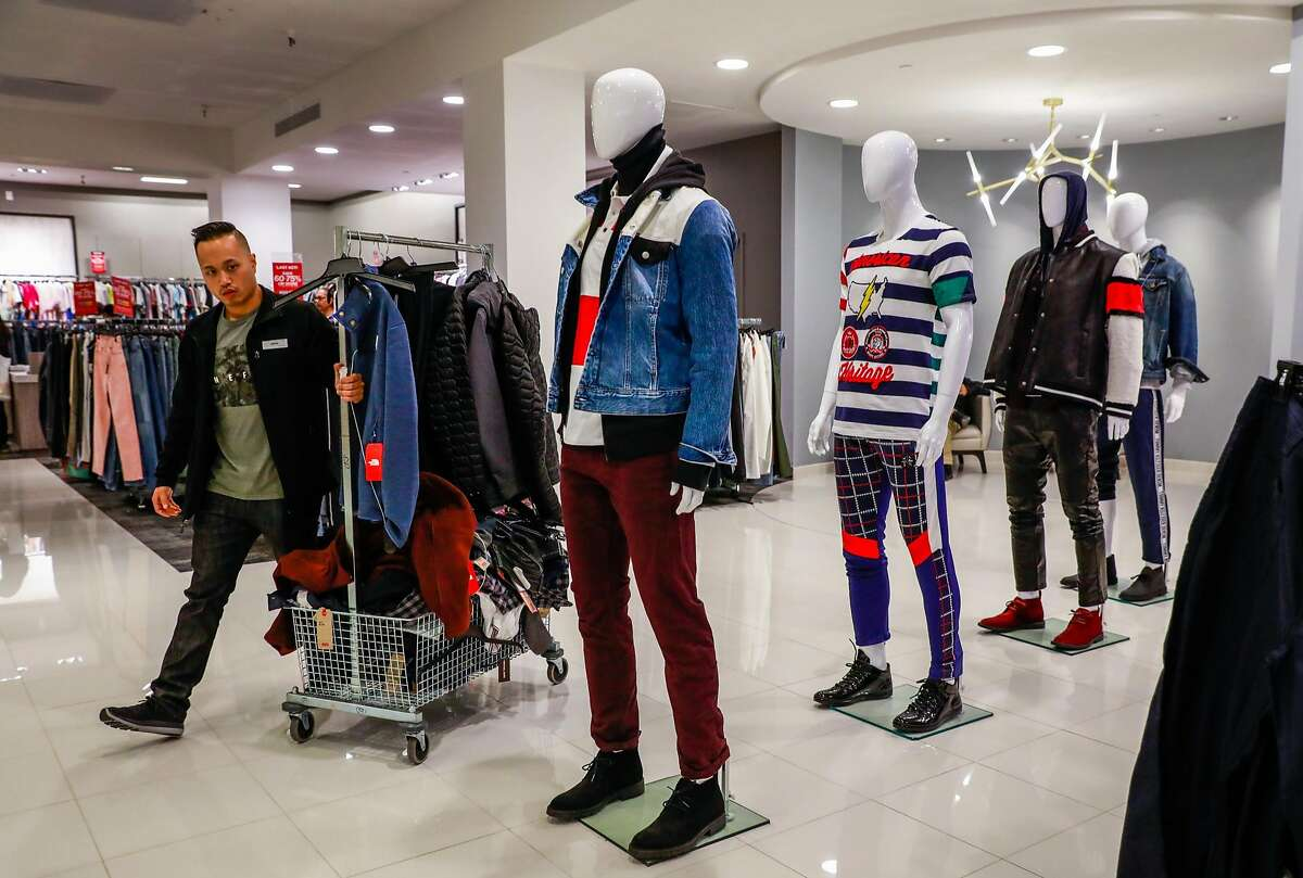 A sales associate carries a rack of clothes through the men's department at Macy's in San Francisco, California, on Tuesday, Oct. 16, 2018.