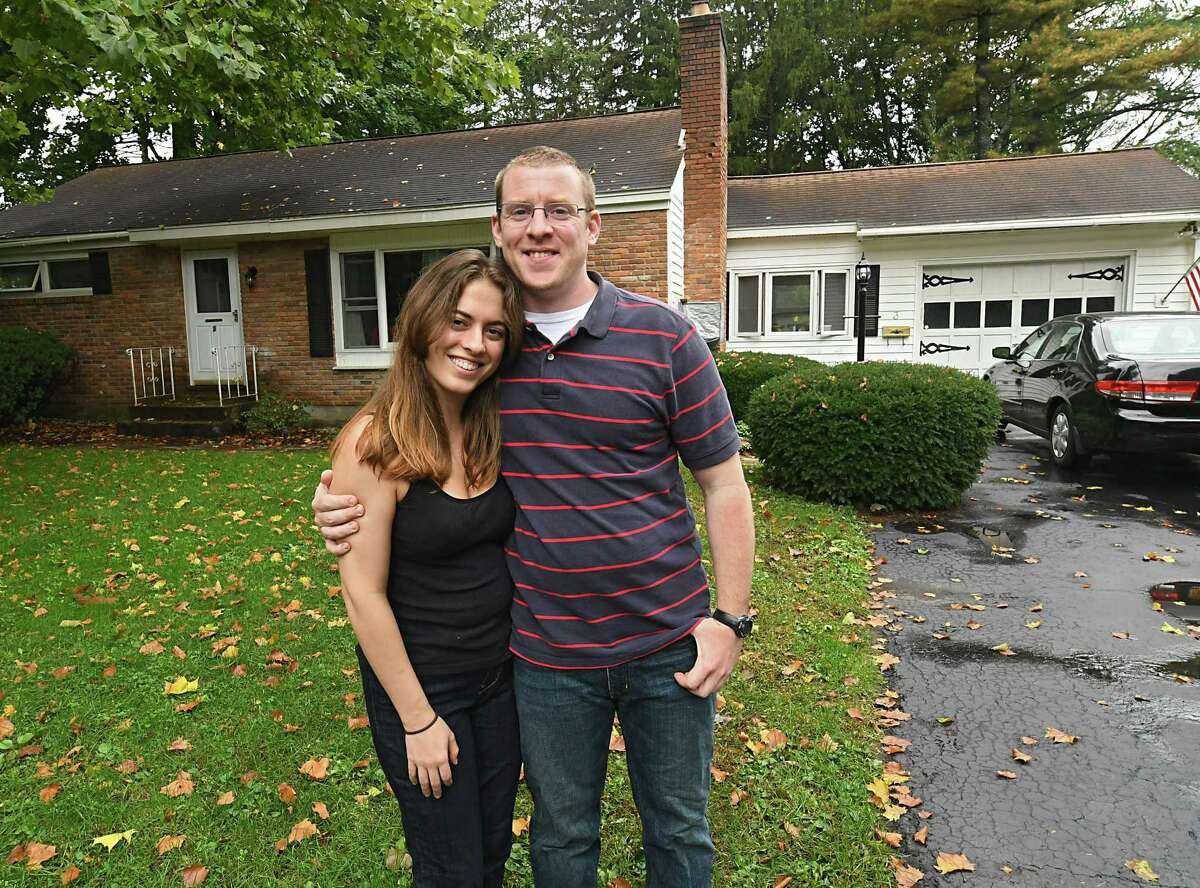 Sara Tracey and Steve Hughes stand in front of the house they bought on Thursday, Oct. 11, 2018 in Glenville, N.Y. The house used to belong to Sara's grandparents. (Lori Van Buren/Times Union)