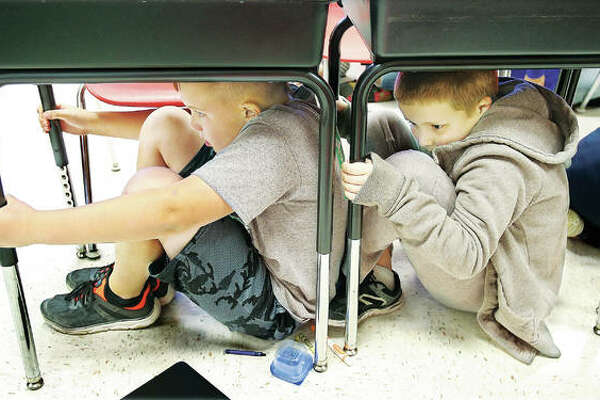 "Students in the fourth-grade classroom of teacher Eric Dickerson perform a little ""duck and cover"" under their desks Thursday as part of an earthquake drill held at North Elementary School in Godfrey. The school has participated every year in The Great U.S. ShakeOut Earthquake Drill Day, learning to make their responses a quick muscle reaction due to the lack of warnings during earthquakes. An estimated 3 million people in the U.S. participated Thursday morning in the drill, and nearly 60 million were expected worldwide. The event is sponsored by several organizations, including FEMA and the American Red Cross."