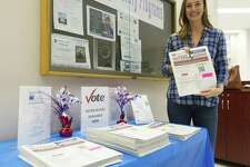 Erin Baker, president of Montgomery County League of Women Voters, poses next to the organization's display of voting guides at the Montgomery County Central Library, Thursday, Oct. 18, 2018, in Conroe. The organization provides non-partisan information about candidates to voters.