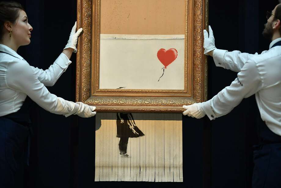 """This painting by artist Banksy entitled """"Love is in the Bin"""", a work that was created when the painting """"Girl with Balloon"""" sold or $1.4 million was passed through a shredder in a surprise intervention by the artist shortly after it was sold.  Photo: BEN STANSALL, AFP/Getty Images"""