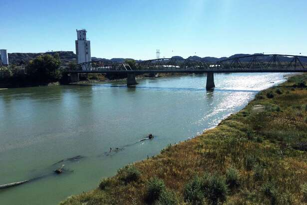 The Yellowstone River flows by a grain tower in Glendive, Mont.