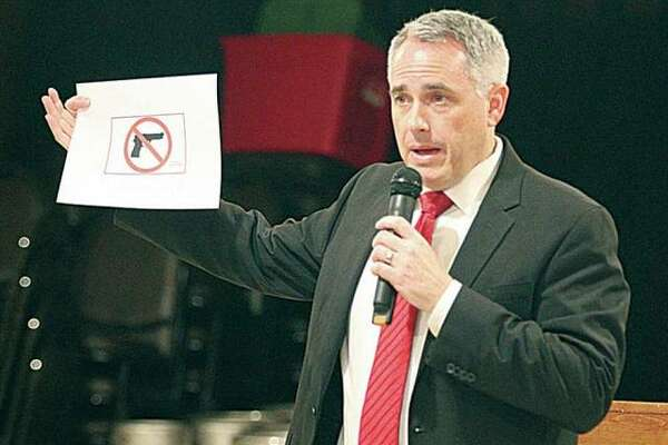 "In this April 2016 file photo, Madison County State's Attorney Tom Gibbons holds a copy of the ""magic sign"" that must be displayed to prohibit people with concealed carry permits from taking firearms into a building."