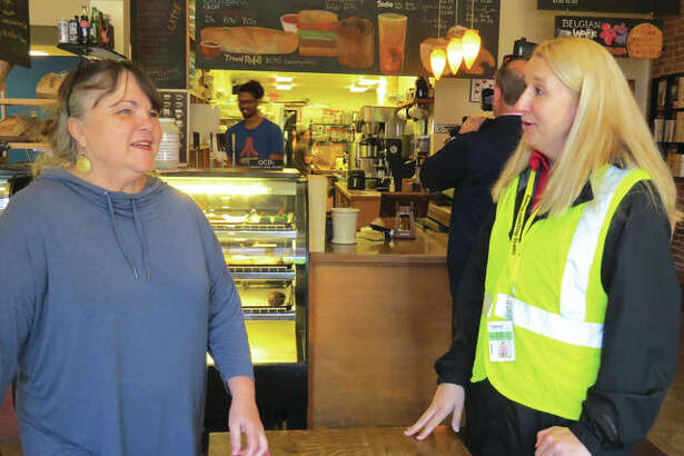 Kimberli Goodner, owner of 222 Artisan Bakery, talks to a representative from Ameren Illinois about a scam that she got caught up in.