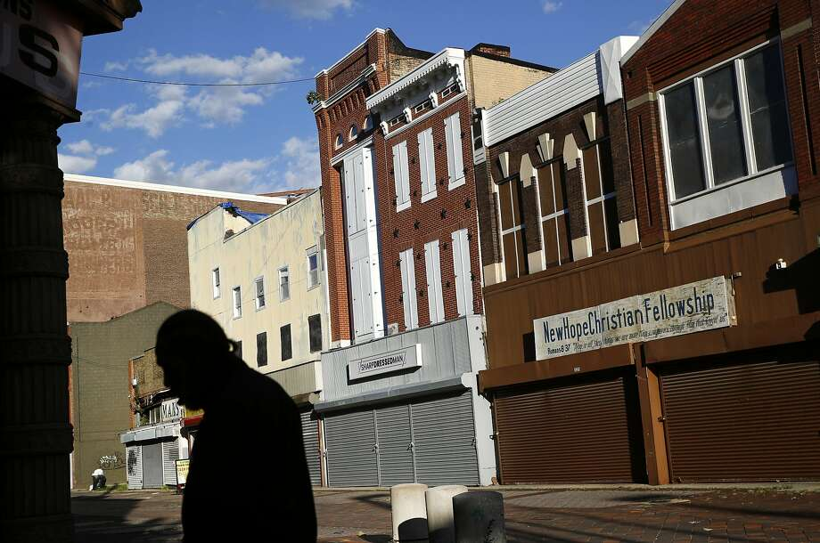 A man walks past vacant storefronts at the Old Town Mall in Baltimore. Photo: Patrick Semansky / Associated Press