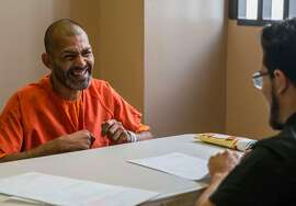 Glenn Dyer Detention Facility inmate Manish Sharma, 38, smiles after registering to vote for the first time with assistance from Alameda County Public Defender's Office Client Advocate Diego Cardenas, right, at Glenn Dyer Detention Facility in Oakland, Calif. Friday, Oct. 12, 2018.