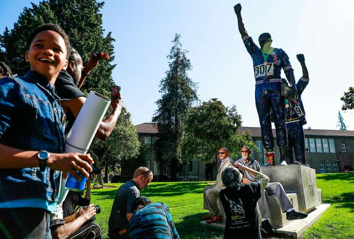 1968 Olympic athletes Tommie Smith and John Carlos sit for a portrait in front of a statue that honors their iconic protests at the 1968 Mexico City Olympics while Tommie's grandson Jakobi Smith,12 looks on (right) at San Jose State University in San Jose, California, on Wednesday, Oct. 17, 2018.