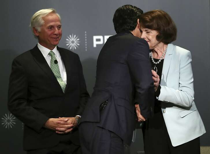 Public Policy Institute of California CEO and debate monitor Mark Baldassare, left, watches as California Sen. Kevin de Leon, D-Los Angeles, embraces California Sen. Dianne Feinstein, D-Calif., at the end of a debate on Wednesday, Oct. 17, 2018, in San Francisco. Feinstein shared the stage with an opponent for the first time since 2000 when she debated state Sen. Kevin de Leon. The two Democrats are facing off in the Nov. 6 election. (AP Photo/Ben Margot)