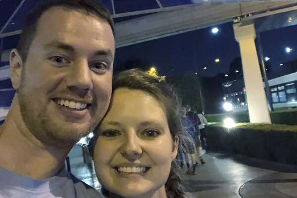 This Oct. 17, 2018 photo provided by Clark Ensminger, shows him with his wife Heather Ensminger at Disneyland in Anaheim, Calif. The couple visited four Disney parks in the Orlando, Fla., area and two Disney parks in the Los Angeles area, with a cross-country flight in between, all within 20 hours and two time-zone changes. (Clark Ensminger via AP)