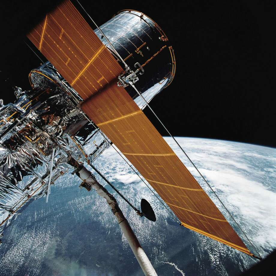 NASA's April 25, 1990, file photo reveals most of the vast Hubble Space Telescope, as seen through Discovery's Remote Manipulator System (RMS) after deploying some of its solar panels and antennas is exposed in space. The Hubble Space Telescope was overridden by a failure of the alignment system. NASA announced on Monday, October 8, 2018, that one of Hubble's gyroscopes will be shut down on Friday, October 5. Hubble is therefore in the so-called safe mode in which it is still orbiting, but not essential systems are turned off. This means that all astronomical observations have been shelved. (NASA via AP, File) Photo: Associated Press / NASA