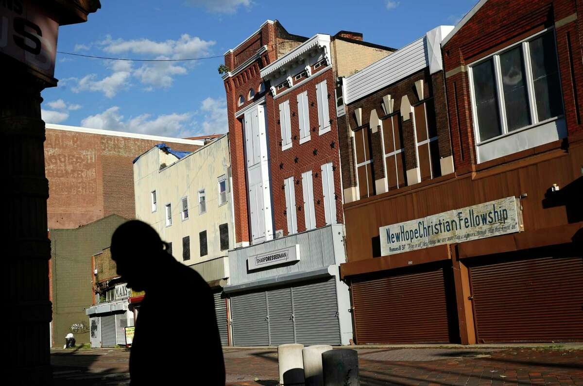 In this Tuesday, Oct. 17, 2018 photo, a man walks past vacant storefronts at the Old Town Mall in Baltimore. Job growth was supposed to be a cure-all to stop the wealth gap from worsening, but new research suggests that impoverished Americans are getting left out even when their communities enjoy hiring booms. (AP Photo/Patrick Semansky)