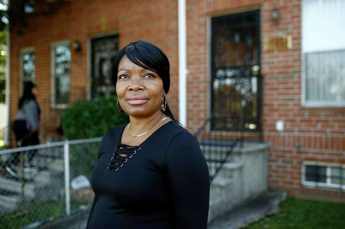 In this Tuesday, Oct. 17, 2018 photo, Octavia Mason poses for a photo outside of her mother's home in Baltimore. Mason's drug use after a broken marriage caused her to lose her license to teach high schoolers to become pharmacy technicians. Now she participates in a program called