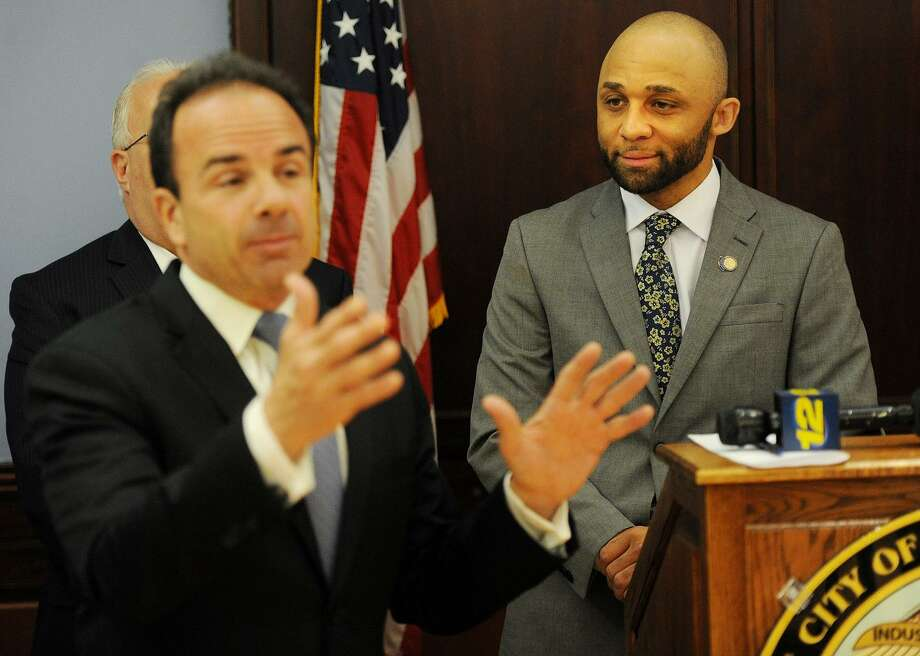 Louis Reed, right, program manager of the Mayor's Initiative for Reentry Affairs, looks on as Bridgeport Mayor Joe Ganim addresses a memorandum granting individuals with prior convictions scholarships to Housatonic Community College's advanced manufacturing certificate program in 2017. Reed is facing 10 years in prison after he pleaded guilty to larceny charges. Photo: Brian A. Pounds / Hearst Connecticut Media / Connecticut Post