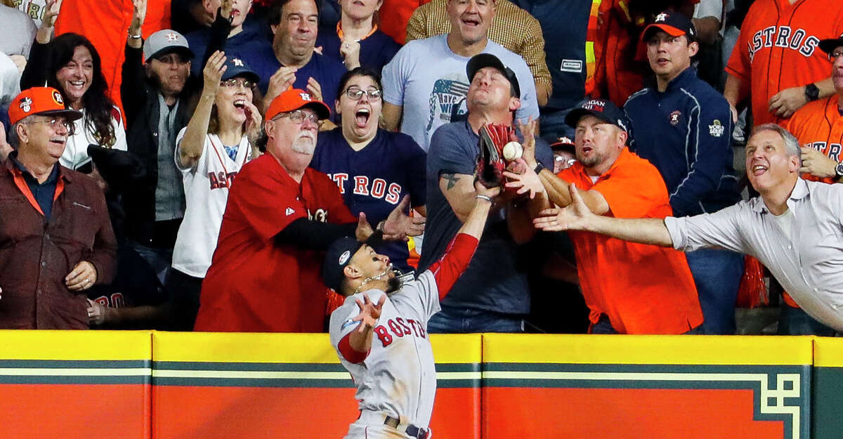 Red Sox right fielder Mookie Betts tries to catch a fly ball by Astros designated hitter Jose Altuve (27) during the first inning of Game 4 of the American League Championship Series on Oct. 17, 2018, in Houston. Altuve was called out on the play due to fan interference, wiping out a two-run home run that would've tied the score at 2.