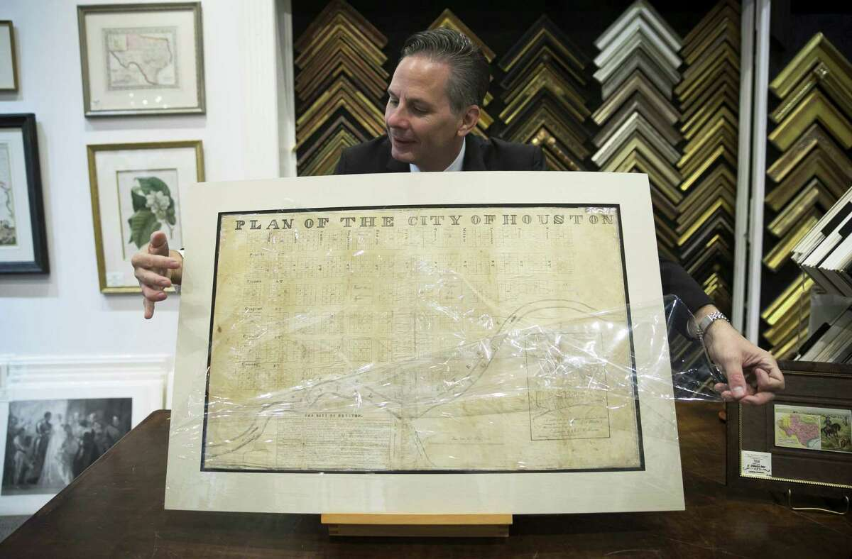 Ed Grusnis, owner of the Antiquarium in River Oaks, opens a plastic seal protecting one of the original maps of Houston created by the Allen brothers in his store on Thursday, Oct. 18, 2018, in Houston.