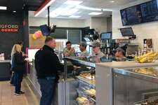 Dunkin' Donuts employees at the 1101 N. Colony Road location in Wallingford wait on a customer Thursday.