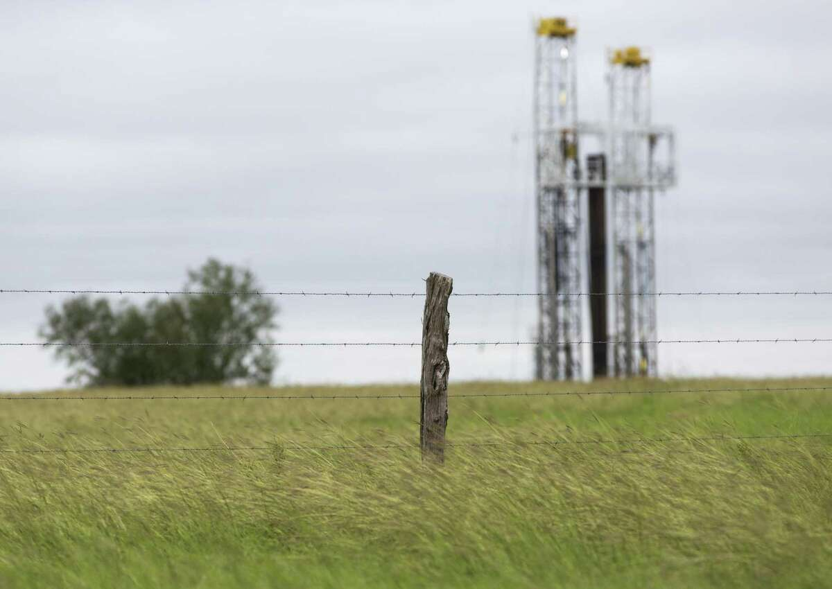 A drilling rig rises Wednesday, Oct. 18, 2018 behind a pasture a few miles outside Kenedy in the heart of the Eagle Ford shale oil play.