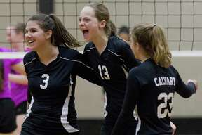 Holland Guisler of Calvary Baptist (3) reacts beisde Hannah Riggens(13) after scoring a point during the third set of a TAPP District 10-1A olleyball match at First Baptist Church of Conroe on Thursday.
