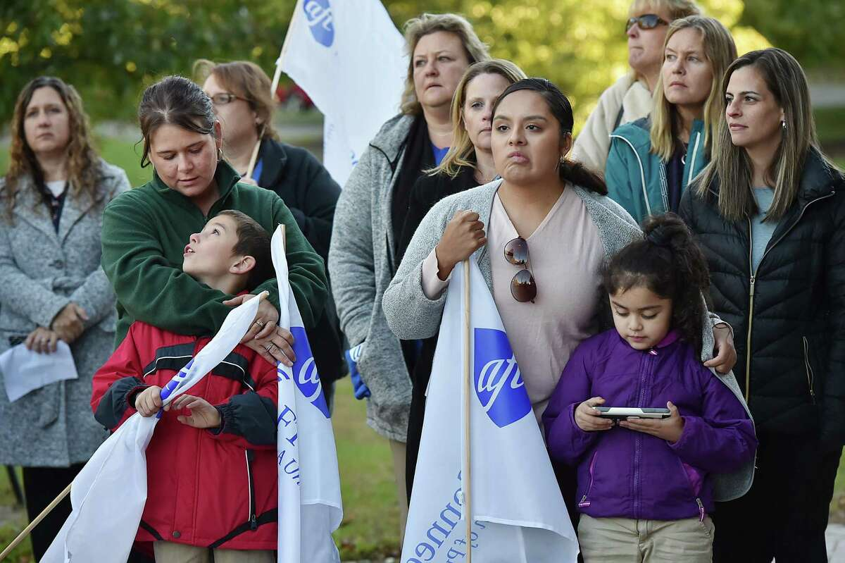 Nicole Childs and her son Austin, 10, and Leslie Navarrete and her daughter Mika Aziz, 6, are surrounded by teachers at a rally held by the Ansonia Federation of Teachers Thursday to drawattention to a legal dispute between the school district and City Hall.