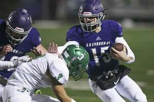 Greyhound quarterback Cole Boyd gets an arm out to fend off Eagle tackler Daniel Valadez in the first half as Boerne hosts Pleasanton on October 18, 2018.