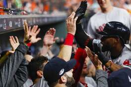 Boston Red Sox Jackie Bradley Jr. (19) is welcomed back to the dugout after hitting a grand slam giving the Red Sox an 8-2 lead in the eighth inning of Game 3 of the American League Championship Series at Minute Maid Park on Tuesday, Oct. 16, 2018, in Houston.