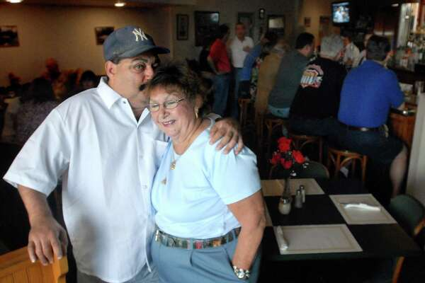 In this 2008 photo, Michael Ippolito gives his mother Bett Ippolito a kiss on their last day at the River Restaurant in Derby.