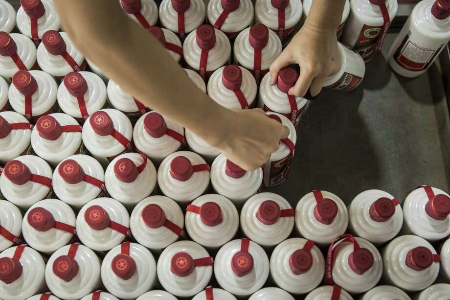 An employee collects bottles of baijiu from a cart at the Kweichow Moutai Co. factory in the town of Maotai in Renhuai, Guizhou province, China, on Dec. 14, 2017. Photo: Qilai Shen/Bloomberg / Bloomberg