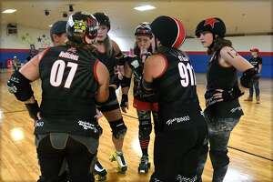"The Conroe Cutthroat's Jaime Gardner aka ""James Blonde #2"", clockwise from left, Leana Welch aka"" ""Burning Ember"", LeAnn Sherbert aka ""C-3KO"", Jennifer Cowart aka """"CT Scan 911"", Angel Rupert aka ""Hellicious 7K"", and Coach Meat strategize during a timeout in their game with the Machete Betties of Houston at Rainbow Roller Rink in Conroe on Oct. 7, 2018."