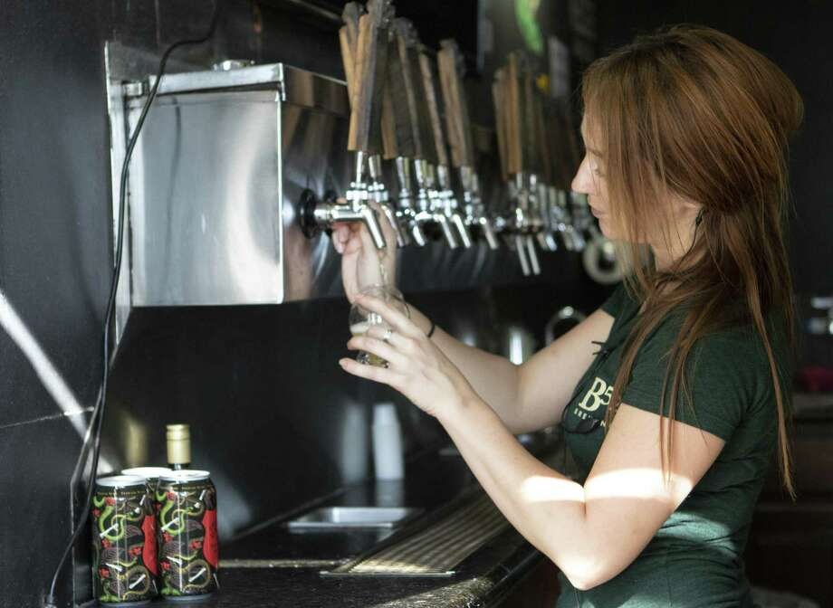 Bartender Angela Babelman pours a brew into a sampler glass Friday, Oct. 12, 2018 at B52 Brewing in Conroe. Photo: Cody Bahn, Houston Chronicle / Staff Photographer / © 2018 Houston Chronicle