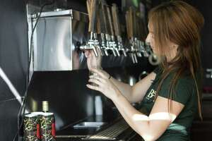 Bartender Angela Babelman pours a brew into a sampler glass Friday, Oct. 12, 2018 at B52 Brewing in Conroe.