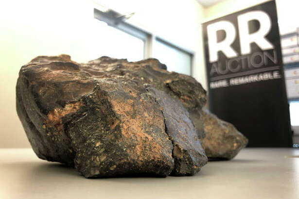 A 12-pound (5.5 kilogram) lunar meteorite discovered in Northwest Africa in 2017 rests on a table, in Amherst, N.H. The rock, which is actually comprised of six fragments that fit together like a puzzle, was found last year in a remote area of Mauritania, but may have plunged to Earth thousands of years ago. The meteorite could sell for $500,000 or more at an online auction that runs from Thursday, Oct. 11, until Oct. 18, 2018. (AP Photo/Rodrique Ngowi)