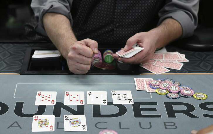 The dealer reveals the board cards during a game of Texas Hold'em at Rounders Card Club, Sunday, Oct. 14, 2018. In the last year, about a dozen poker clubs have opened in San Antonio. Their legal status remains unresolved.