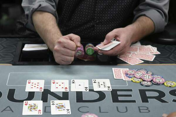 The dealer reveals the board cards during a game of Texas Hold?'em at Rounders Card Club, Sunday, Oct. 14, 2018. In the last year, about a dozen poker clubs have opened in San Antonio. Their legal status remains unresolved.