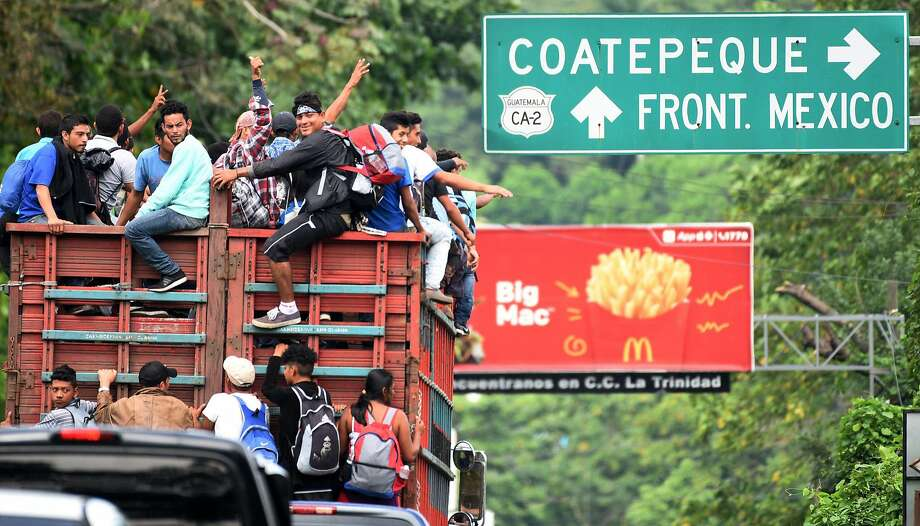 Honduran migrants onboard a truck in direction to Tecun Uman, in the border with Mexico, take part in a caravan heading to the US, in Coatepeque, Quetzaltenango department, on October 19, 2018. - Honduran migrants who have made their way through Central America were gathering at Guatemala's northern border with Mexico on Friday, despite President Donald Trump's threat to deploy the military to stop them entering the United States. (Photo by ORLANDO SIERRA / AFP)ORLANDO SIERRA/AFP/Getty Images Photo: ORLANDO SIERRA;Orlando Sierra / AFP / Getty Images