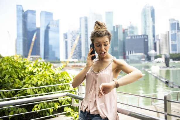 Worried woman talking on smart phone, checking the time, skyscrapers and marina on background.