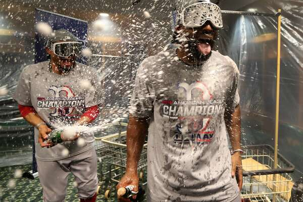 Boston Red Sox No. 50 Mookie Betts and No. 19 Jackie Bradley, Jr. partied with clubhouse champagne after a decisive victory against the Houston Astros. (Photo by Jim Davis/The Boston Globe via Getty Images)