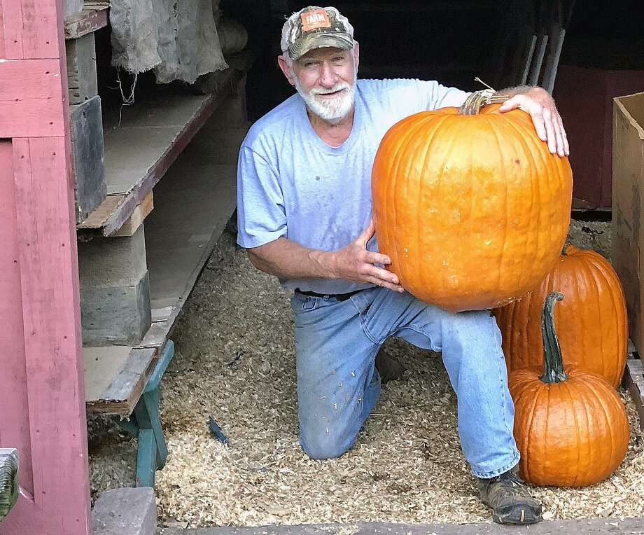 Harvey Smith with the Dilly-of-a-Jack pumpkin he grew at Strawberry Hollow Farm in Guilford. Photo: Lisa Reisman / For Hearst Connecticut Media / New Haven Register freelance