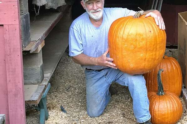 Harvey Smith with the Dilly-of-a-Jack pumpkin he grew at Strawberry Hollow Farm in Guilford.
