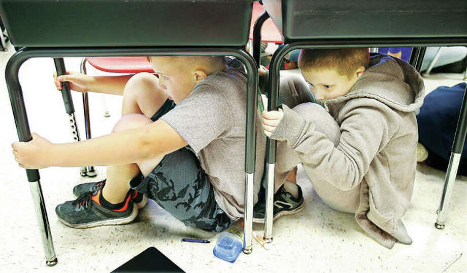 "Students in the fourth-grade classroom of teacher Eric Dickerson perform a little ""duck and cover"" under their desks Thursday as part of an earthquake drill held at North Elementary School in Godfrey. Photo: John Badman 