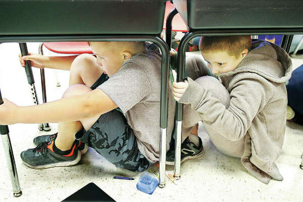 "Students in the fourth-grade classroom of teacher Eric Dickerson perform a little ""duck and cover"" under their desks Thursday as part of an earthquake drill held at North Elementary School in Godfrey."