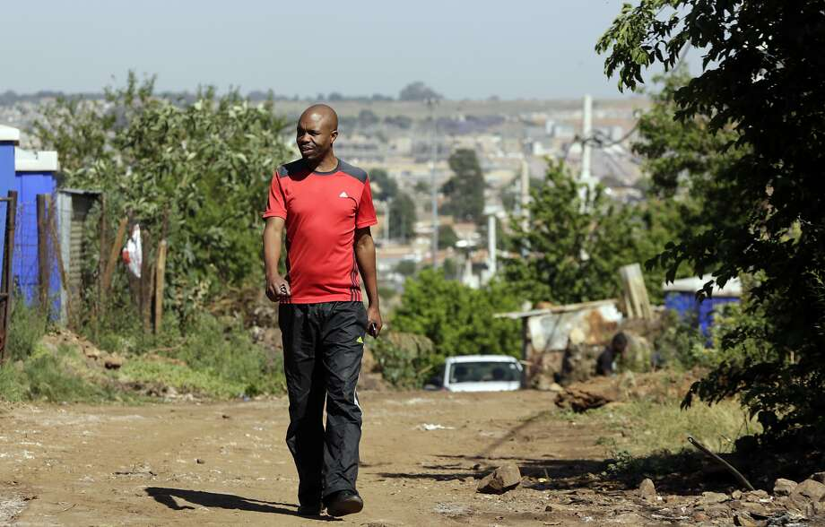 Somsy Matso, who wants to expand low-cost housing, walks in a settlement in Tembisa, South Africa. Photo: Themba Hadebe / Associated Press