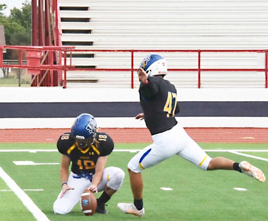 HOLD IT DOWN Wayland Baptist junior Caden Bailey holds the football steady as sophomore Edgar Baeza kicks an extra point for the Pioneers during its four-overtime win over Lyon College on Oct. 6 at Greg Sherwood Memorial Stadium in Plainview. After a week off, the Pioneers play Texas College in Tyler. Photo: Claudia Lusk/Wayland Baptist University